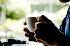 Stäng sig upp av mannen som rymmer den varma lattekaffekoppen för avbrottstid Royaltyfria Foton