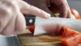Stäng sig upp av mannen som skivar tomater med kniven arkivfilmer