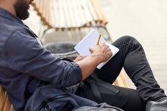 Stäng sig upp av mannen som skriver till anteckningsboken på stadsgatan Arkivfoton