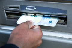 Stäng sig upp av mannen som tar kassa från ATM med kreditkorten Fotografering för Bildbyråer