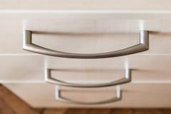 Stäng sig upp av metallhandtaget av en enhet Modern träbyrå av ljus färg Begrepp av minimalist hem- möblemang royaltyfri foto
