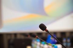 Stäng sig upp av mikrofonen i mötesrum för konferens effekt för 50mm bakgrundsblur aktiverar sidan för nattnikkordeltagaren Royaltyfria Bilder