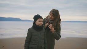 Stäng sig upp av moder och son i varm kläder som bakom står på kusten samman med havet Modern säger arkivfilmer