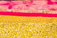 Stäng sig upp av olikt tyg av olika färger, väntande på sömnadkläder för tyg och annan saker, rött gult tyg Royaltyfria Bilder