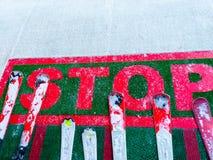 Stäng sig upp av ordstoppet som varnar till skidåkare att de måste stoppa på det ställe Några skidar utrustningar med vit snö på  royaltyfri foto