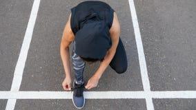 Stäng sig upp av passformkvinnan som binder skosnöre, medan stå på asfaltvägen under, joggar i sommarafton royaltyfri bild