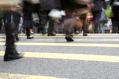 Stäng sig upp av pendlarefot som korsar den upptagna gatan Arkivfoton