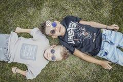 Stäng sig upp av pojkar, bröder som ligger i parkera på grönt gräs ovanför sikt royaltyfri foto