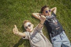 Stäng sig upp av pojkar, bröder som ligger i parkera på grönt gräs ovanför sikt royaltyfri bild