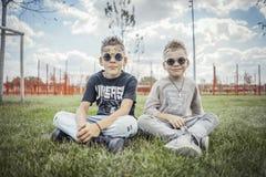 Stäng sig upp av pojkar som sitter i parkera på grönt gräs arkivfoto