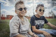 Stäng sig upp av pojkar som sitter i parkera på grönt gräs lycklig begreppsfamilj royaltyfri foto