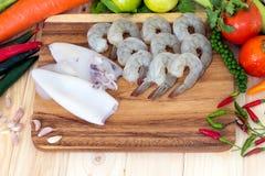 Stäng sig upp av räka, tioarmad bläckfisk, och nya grönsaker på träkvarteret för förbereder matlagning Royaltyfri Foto