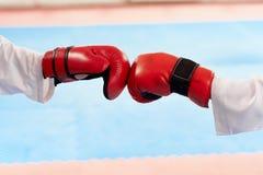 Stäng sig upp av röda boxninghandskar som tillsammans slår på ljus grupp arkivbilder