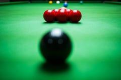Stäng sig upp av röda och svarta bollar på snookertabellen royaltyfria bilder