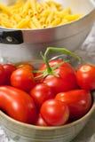 Stäng sig upp av röda tomater i en bunke och ett filter mycket av pasta Royaltyfria Bilder
