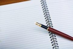 Stäng sig upp av reservoarpenna eller bläckpenna med anteckningsbokpapper på woode Fotografering för Bildbyråer
