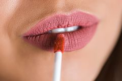 Stäng sig upp av rosa kanter av flickan, ung härlig kvinna applicerad läppstift naturlig makeup Skönhetsmedel arkivbild