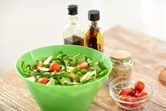 Stäng sig upp av salladbunken och kryddor på köksbordet Arkivfoton
