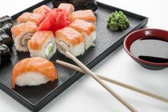 Stäng sig upp av sashimisushiuppsättning med pinnar och sojabönor på ett tjänande som magasin royaltyfri fotografi