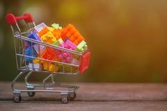 Stäng sig upp av shoppingvagnen mycket av legos arkivfoto
