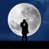 Stäng sig upp av silhouettepar som kysser på fullmånen Royaltyfri Bild