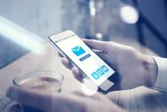 Stäng sig upp av smartphoneinnehav i kvinnlig hand Skärm för Emailapp-manöverenhet Koppespresso på tabellen som är horisontal arkivbilder