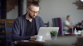 Stäng sig upp av stilig man i glasögon, svart t-skjorta och sammanträde för blått omslag i kafé genom att använda den moderna bär arkivfilmer