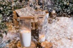 Stäng sig upp av stora stearinljus i glass vaser nära gran-träd medan snowien Arkivfoton