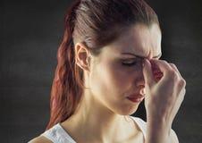 Stäng sig upp av stressad kvinna mot den gråa väggen Arkivbild