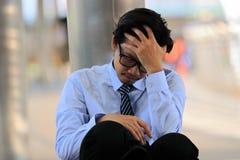 Stäng sig upp av stressad ung asiatisk affärsman med handen på pannasammanträde på golv Mening evakuerat och huvudvärk mot jobb Arkivfoto