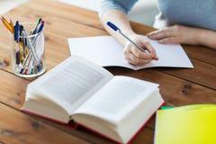 Stäng sig upp av student med boken och anteckningsboken hemma Royaltyfri Fotografi