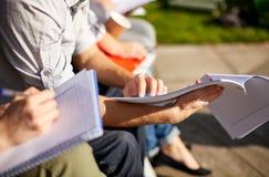 Stäng sig upp av studenter med anteckningsböcker på universitetsområdet Royaltyfri Fotografi