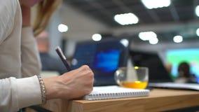 Stäng sig upp av studenter som skriver i en amfiteater STÄNG SIG UPP av kvinnlign som tar anmärkningar i föreläsningsteater mot lager videofilmer