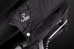Stäng sig upp av svart jeans med tecknet Sale som hänger på kläderkuggebakgrund friday Royaltyfri Bild