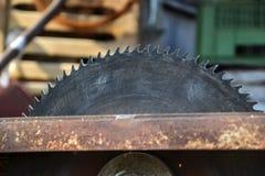 Stäng sig upp av tabellcirkelsågbladet i seminarium Träverk arbetsfaror Farlig sågtandad tablesaw Arkivfoto