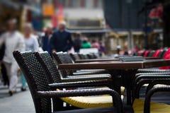 Stäng sig upp av tabeller av restaurangen med folk som går förbi i bet Royaltyfri Fotografi