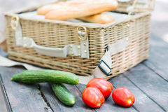 Stäng sig upp av tomater och gurkor över trätabellen framme av en öppen picknickkorg Arkivfoto