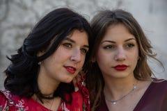 Stäng sig upp av två flickvänner, en blondin och den annan brunetten, serie royaltyfri bild
