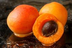 Stäng sig upp av två och halvan skivade frukter för en aprikos med stenen, nytt tvättat med vattendroppar på en mörk bakgrund Royaltyfria Bilder