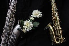 Stäng sig upp av två saxofoner som dekoreras med blommor arkivfoto