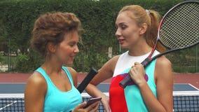 Stäng sig upp av två tennisflickor som diskuterar, medan dela en smartphone lager videofilmer