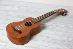 Stäng sig upp av ukulelet på gammal träbakgrund Royaltyfri Foto
