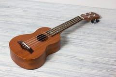 Stäng sig upp av ukulelet på gammal träbakgrund Royaltyfria Bilder