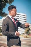 Stäng sig upp av ung en och den attraktiva svarta affärsmannen som går till och med en övergångsställe och framme talar vid telef fotografering för bildbyråer