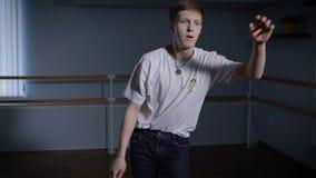 Stäng sig upp av ung höft-flygtur dansare i svart byxa och vita skjortan som utför toprock och andra beståndsdelar av breakdancen lager videofilmer