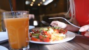 Stäng sig upp av ung kvinna för händer i den röda klänningen som har matställen i ett kafé Ny sallad med tomater, gurkor, chees lager videofilmer