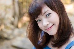 Stäng sig upp av ung nätt asiatisk kvinna i trädgården royaltyfri fotografi