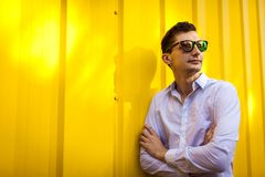 Stäng sig upp av ung stilfull man i det vita skjortaanseendet mot den gula väggen utomhus Trendig dräkt för sommar arkivfoto