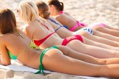 Stäng sig upp av unga kvinnor som ligger på stranden Arkivbild