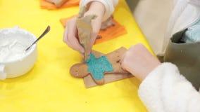 Stäng sig upp av ungen som dekorerar pepparkakakakorna stock video